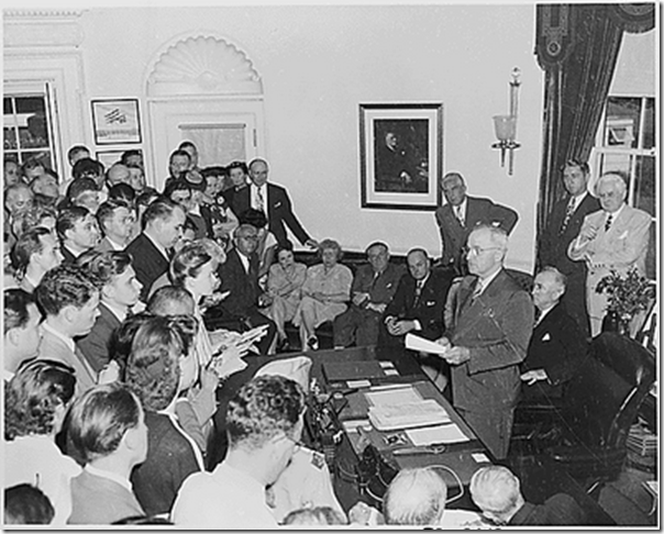 President Truman in the Oval Office, reading the announcement of Japan's surrender